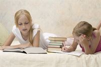 Two sisters do homework on sofa